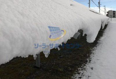 太陽光パネルの端から雪が落ちそうになっている写真