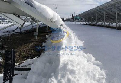 太陽光パネルから落ちた雪が山となり、これ以上自然に落ちにくくなっている様子