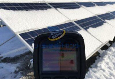 雪の積もった太陽光パネルをサーモグラフィーで測定している写真