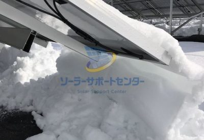 太陽光パネルから落ちた雪が積み上がっている写真