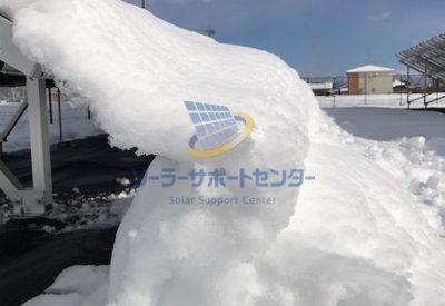 太陽光パネルから自然に落ちた雪が積み上がった写真