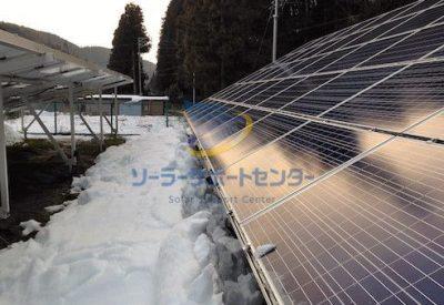 雪下ろし後の太陽光パネルと、パネルの前に積もった雪の写真