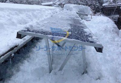 太陽光パネルの雪下ろし作業途中