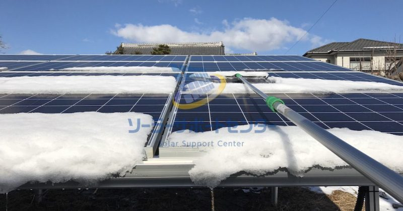 太陽光パネルに積もった雪をおろす作業写真