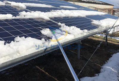 水切りで太陽光パネルの上に残った雪をおろす写真