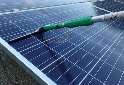 太陽光パネルを水切りで清掃する写真